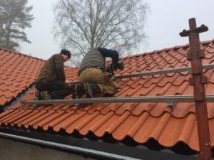 Fredrik och Henke monterar skenor till solpanelerna vid Knektbacken